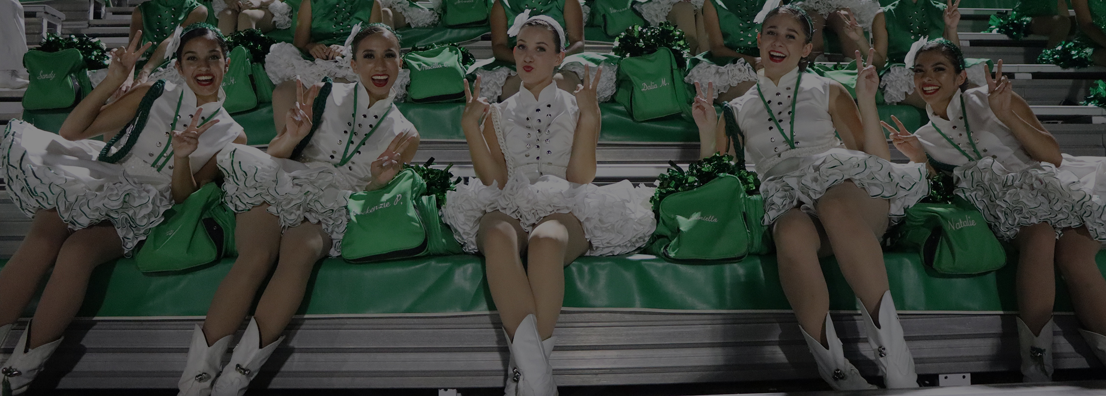 Young cheerleaders posing inwhite and green uniforms on the bleachers